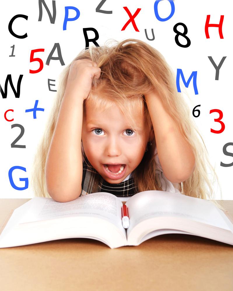 foto kind met boek voor zich met handen op hoofd