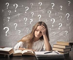 Meisje dat aan het studeren is met haar hand voor haar hoofd. Op het krijtbord achter haar staan vele vraagtekens.