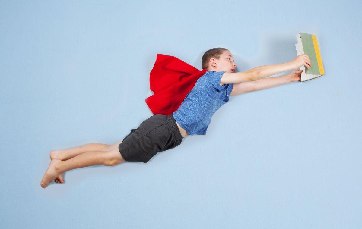 Foto vliegend kind met boek en cape