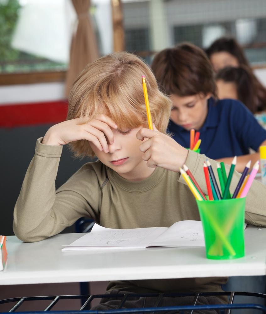 Blonde jongen zit aan een tafel gebogen over een schrift met een potlood in zijn hand