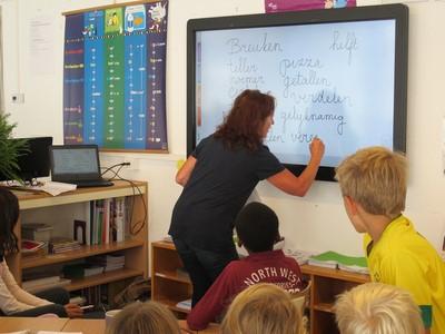 foto van een leerkracht die op het whiteboard rekentermen schrijft