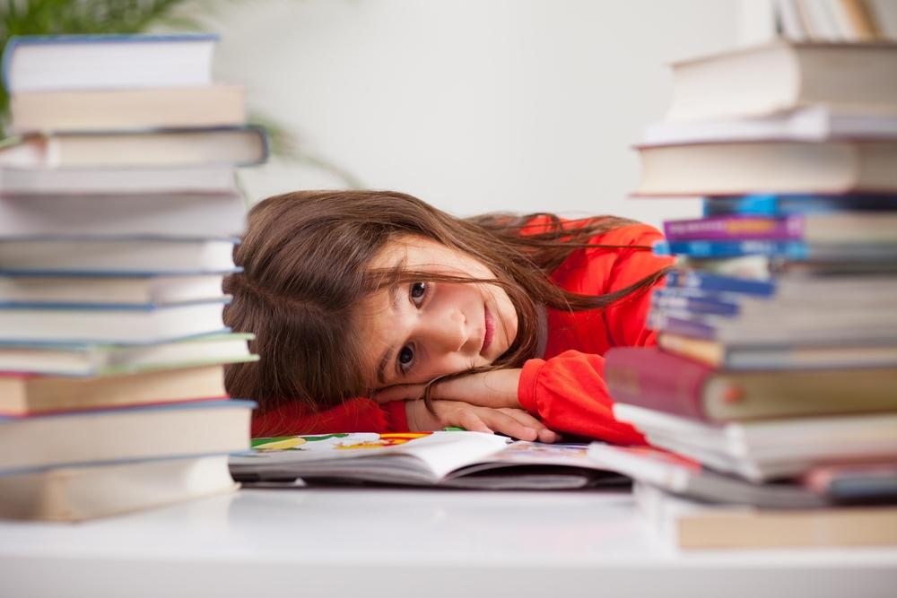 foto's van een kindje dat met zijn hoofd op een boek ligt tussen stapels boeken