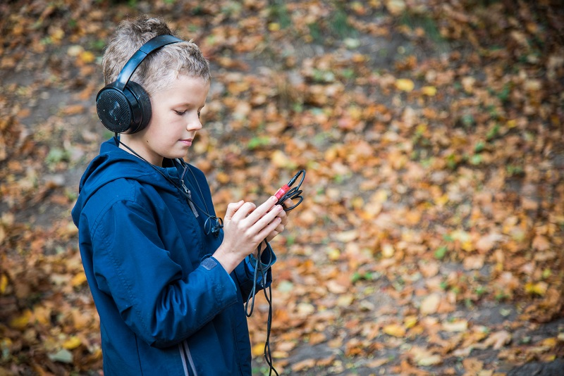 Afbeelding jongen met een Luisterboek op zijn telefoon in het bos