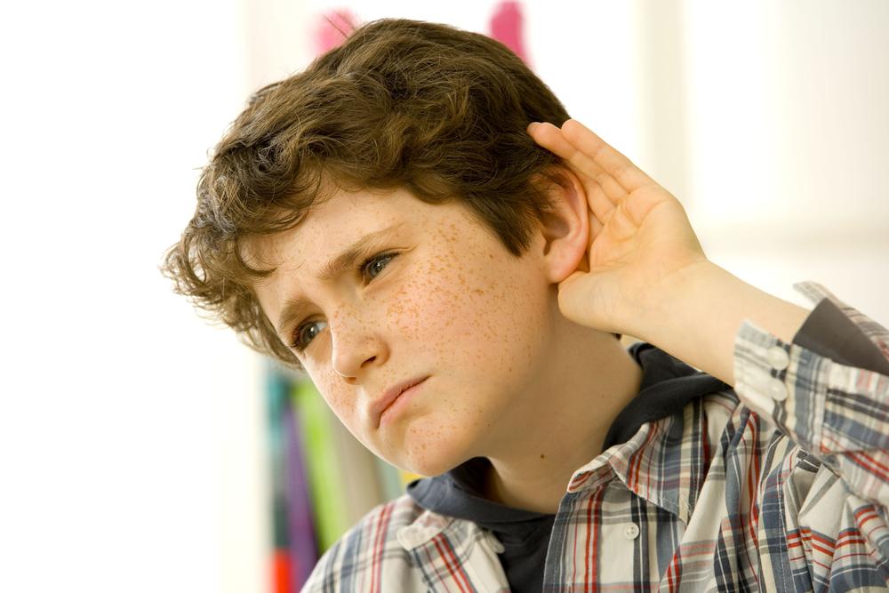 jongen met hand achter zijn oor