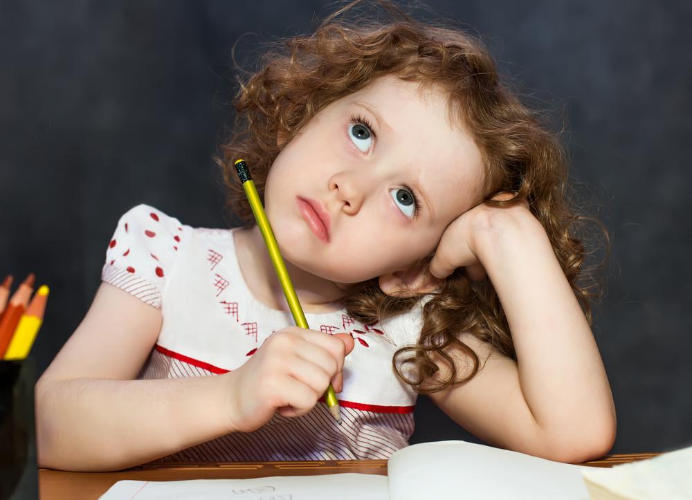 Nadenkend meisje heeft potlood in haar hand