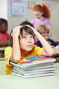 Jongen die in de klas zit met zijn schoolboeken voor hem op de bank, zijn handen voor zijn hoofd.