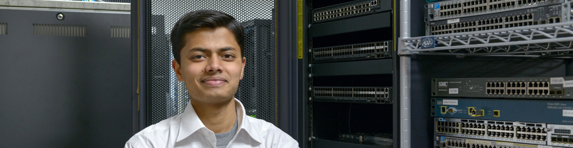 IOL employee Ashnav Lal stands in front of the OCP racks