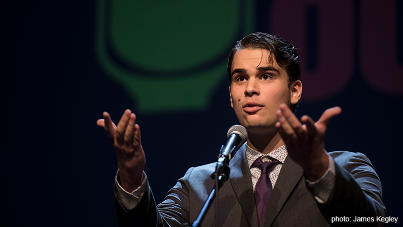 A competitor at the Poetry Out Loud National finals standing at a microphone with raised hands. Photo: James Kegley
