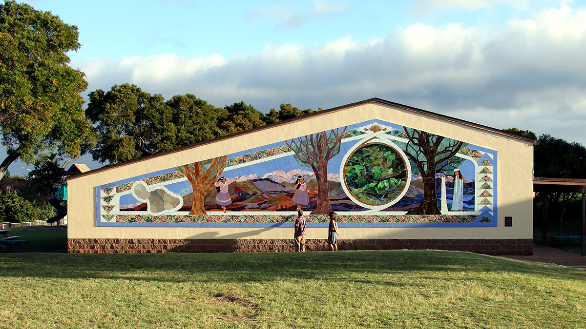 View of mural on building with two people standing in front of it