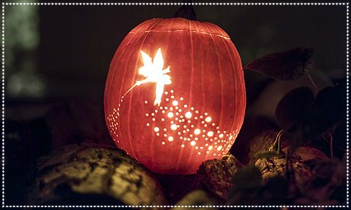 Pumpkin lit from inside with carved Tinkerbell & fairy dust