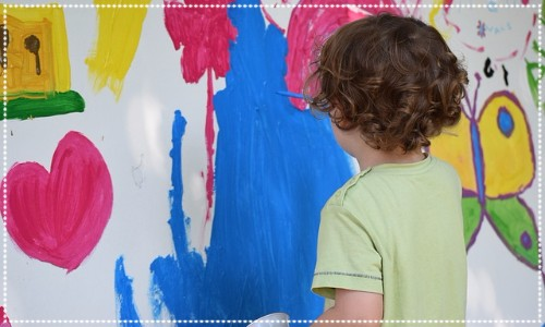 Child painting with bright colours