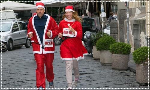 Two people dressed as santa running