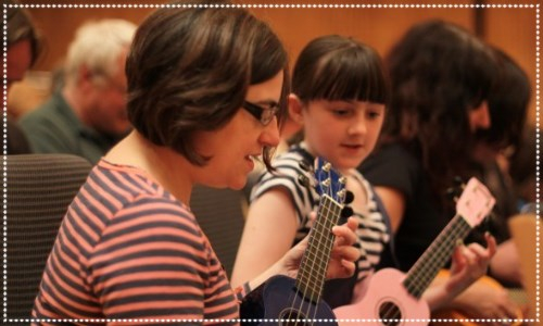 A mother and daughter play the ukulele