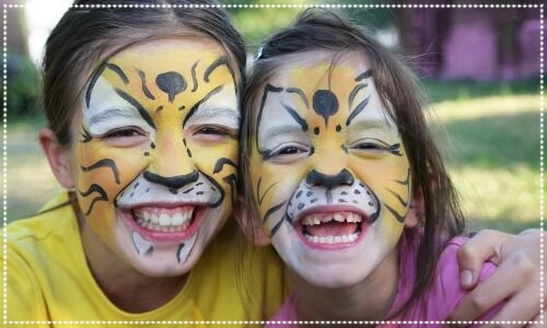 Two children with their face painted as tigers
