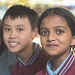 2 young kids in school uniform looking at the camera and smiling