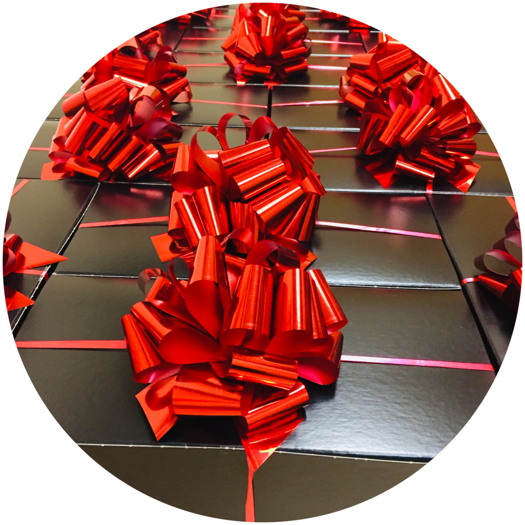 Image of black gift boxes with bright red bows.
