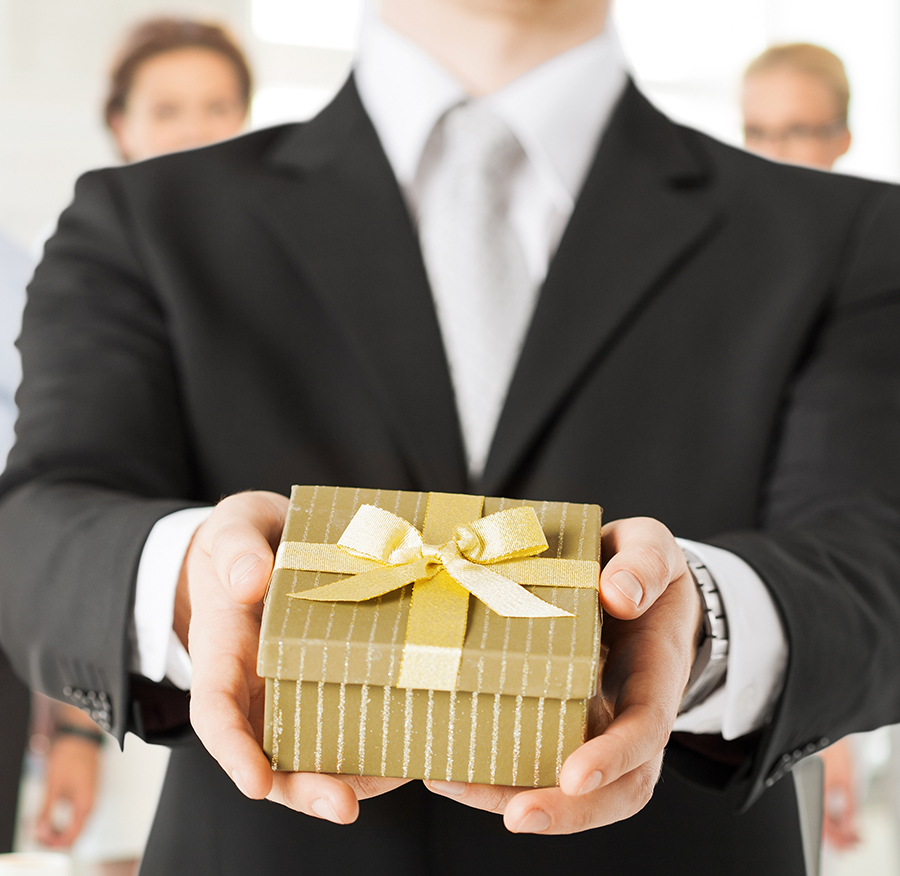 Image of a person in a suit presenting a small gift with both hands.