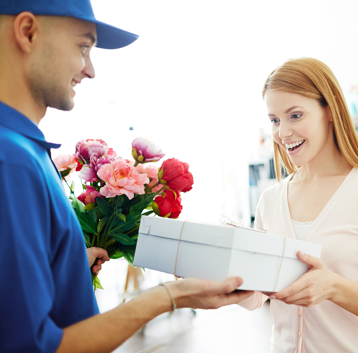 Image of a man handing a gift box and bouquet to a woman.