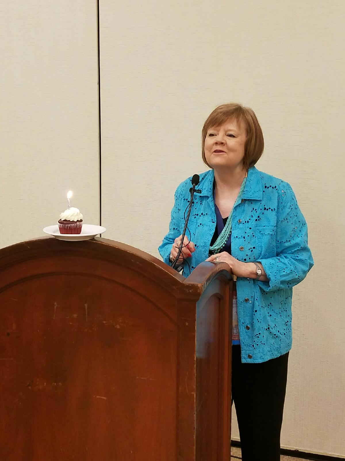 Colorado House Speaker Dickey Lee Hullinghorst is given a cupcake with a candle aflame in honor of her birthday today in Philadelphia at the Colorado delegation breakfast. (Photo by Pat Duncan/The Colorado Statesman).
