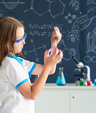 A girl looking at a flask infront of a chalkboard with scientific drawings on