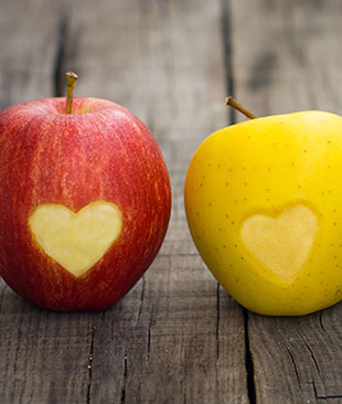 A red and a yellow apple with a heart shape carved out of them