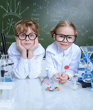 A boy and girl in lab coats with experiments on the desk and a chalkboard of equations behind