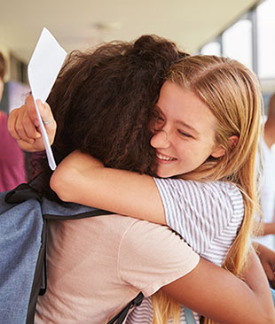 Two teenage girls hugging each other holding a piece of paper