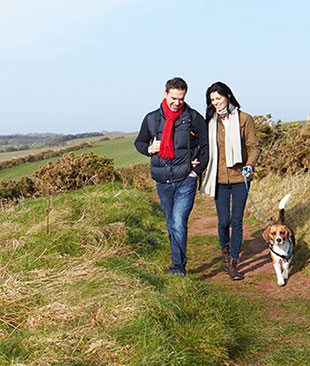 A couple walking with their dog along a coast path