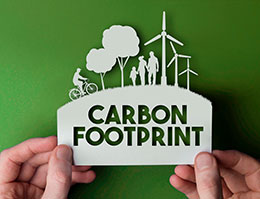 Hands holding a card with the word carbon footprint on it