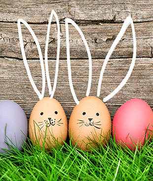 Eggs on grass with rabbit faces drawn on and ears chalked on the boards behind