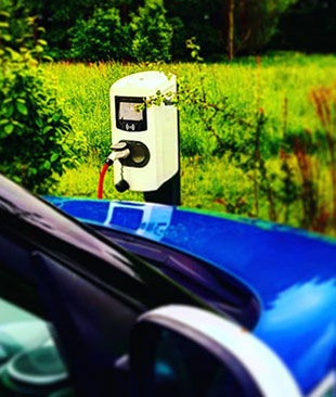A blue car at a electric charge point