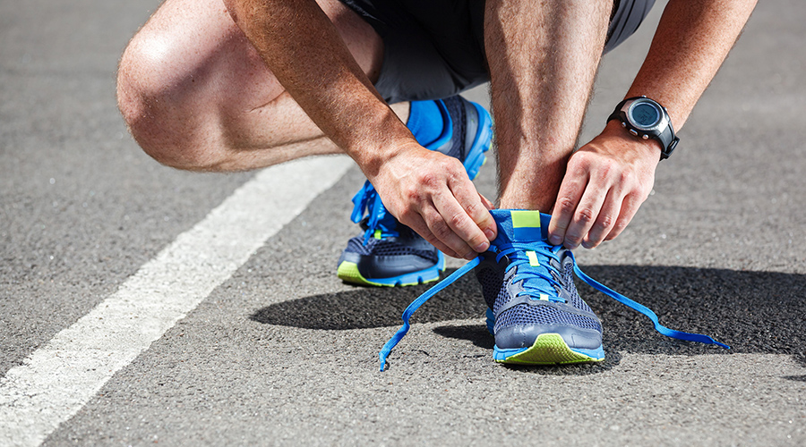 Picture of a runner tying his shoe.