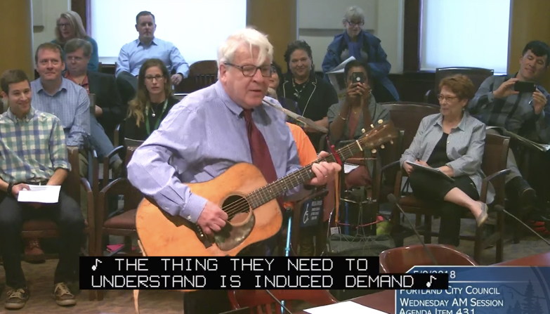 Image shows Paul Rippey testifying with his guitar at Portland City Council