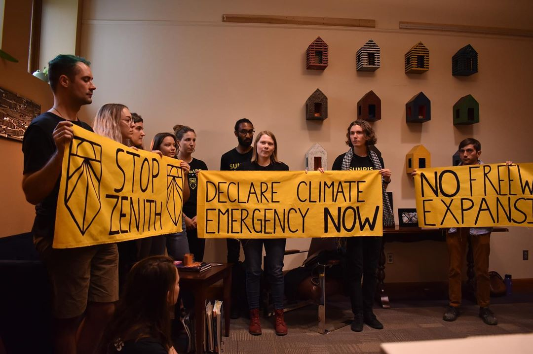 "Image shows Sunrise Movement PDX Youth holding signs in a sit-in at Mayor Wheeler's office, demanding ""No Freeway Expansions"""