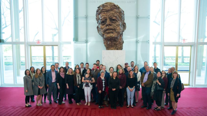attendees of trinity on tour in front of jfk statue