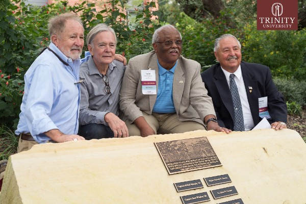 Erich Menger '66, Jerome R. Schmidt '68, Israel P. Anderson '68, and Roberto Valle '68 kneeling in front of memorial plaque