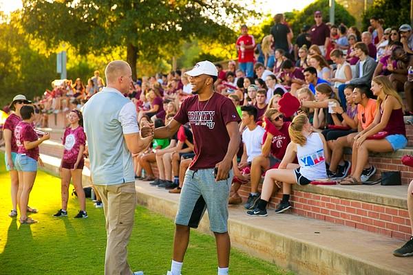Coach Urban congratulating student at rally