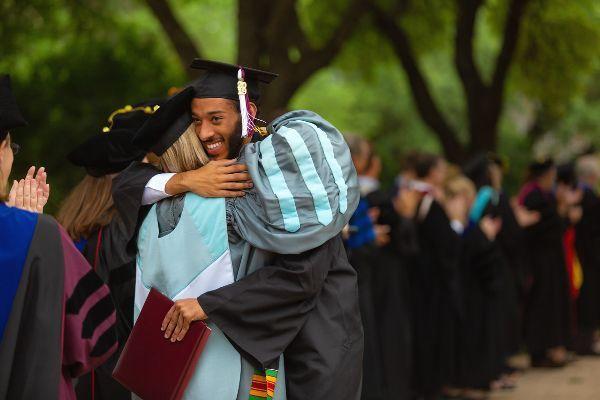 Graduate hugging professor