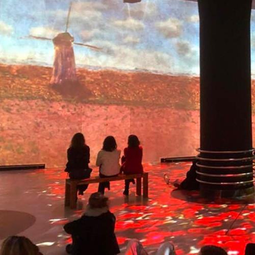 3 vrouwen op een bankje kijken naar een schilderij van Monet