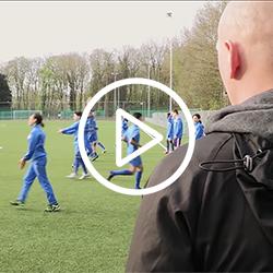 voetbalcoach op een veld met spelers