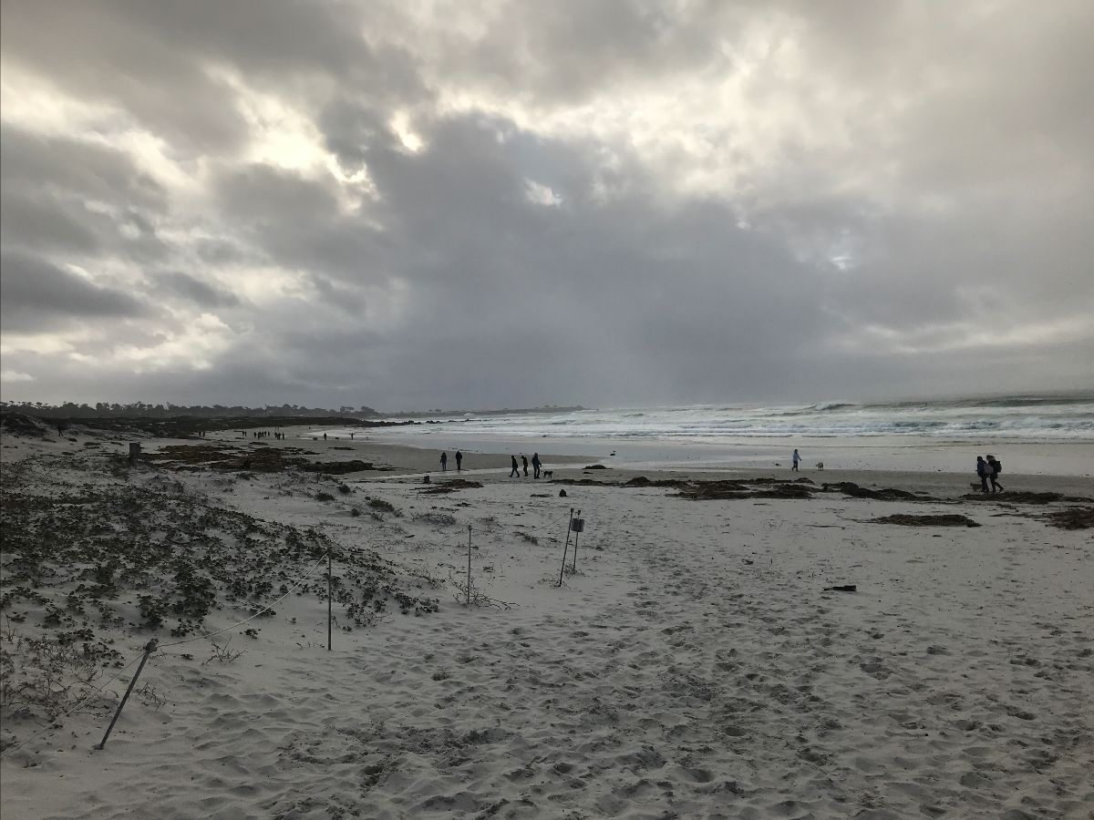 photo of people walking along the beach under stormy skies at Asilomar