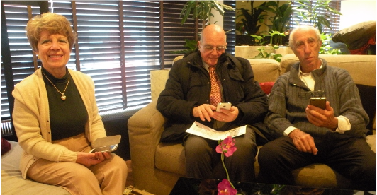 Three seniors with their smartphones sitting on a sofa