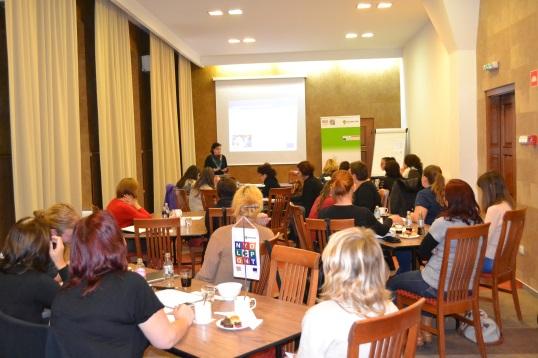 A workshop résztvevői körbeülnek az asztaloknál és figyelnek