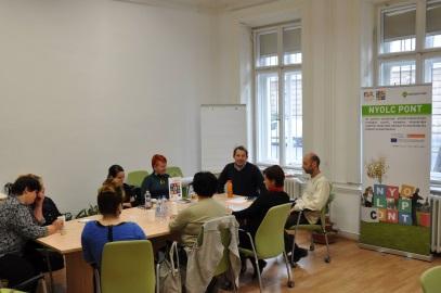Munkacsoport körbeül egy asztalnál és tárgyal