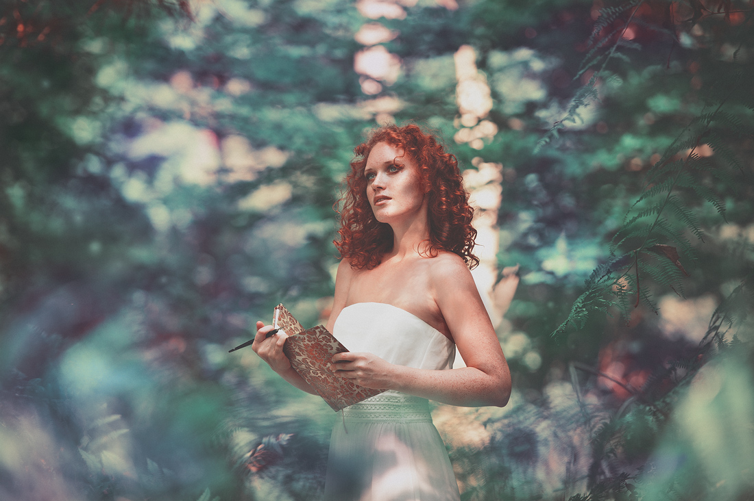 Model with book and pencil standing in a beautiful forest