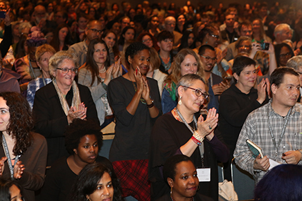 Writers clapping during the conference's keynote address