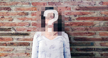 Woman standing against a brick wall. Her face is blurred and obscured by a large question mark.