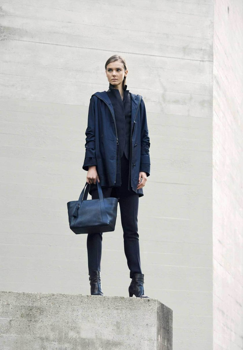 Lady wearing navy Cashmere coat and small Tote Bag