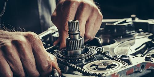 Man's hands working on mechanical gears