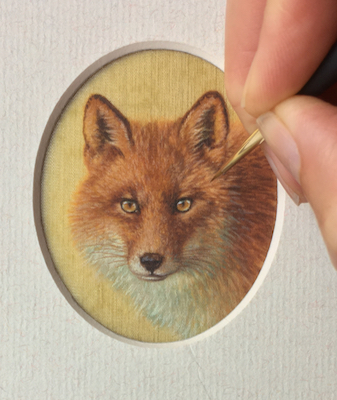 Rachelle Siegrist painting on a miniature of a red fox on silk